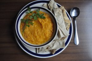 A bowl of carrot soup with Lebanese bread to serve